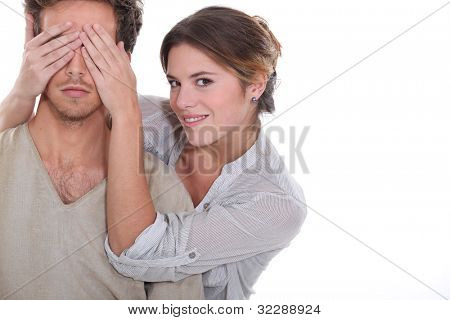 Woman covering partners eyes