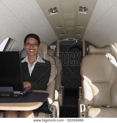 Businesswoman working on laptop inside airplane