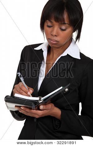Fed-up businesswoman writing in her agenda