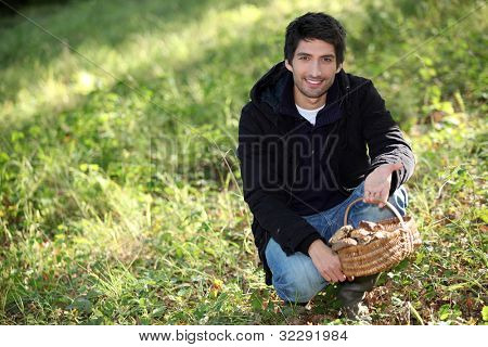 Man knelt by basket of mushrooms
