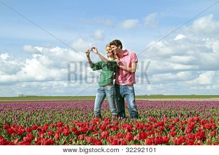 Young happy couple making a picture in the tulip fields from the Netherlands