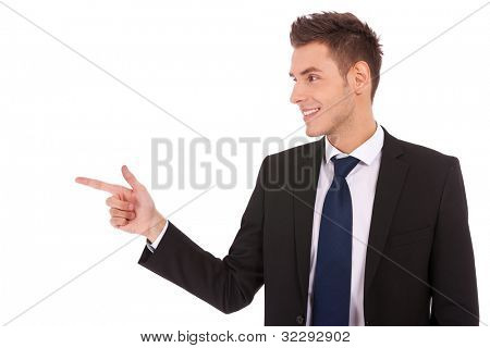 Portrait of a young business man pointing to the side , showing you something