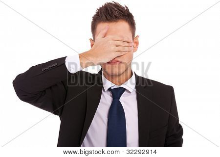 business man making the see no evil gesture over white . young businessman covering his eyes with his hand