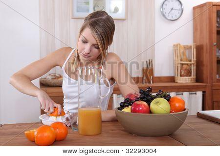 Linda rubia presionando naranja para el desayuno