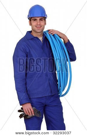 Man carrying coil of piping
