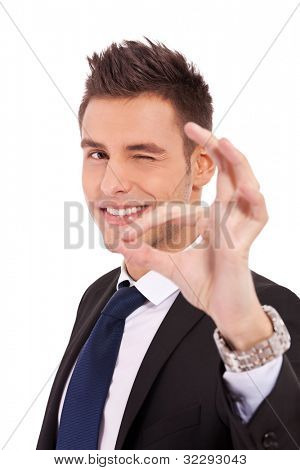 Business man winking at you while doing the ok sign on white background
