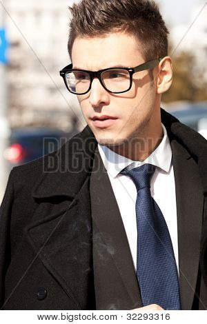 young businessman wearing glasses and looking to a side , outdoor picture