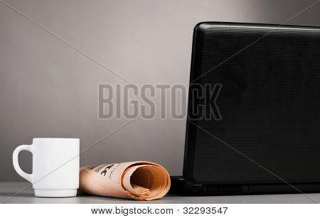 morning workplace of a businessman with laptop, paper and cup