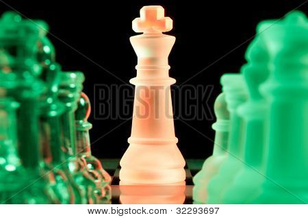 red king and rows of green glass chess pieces is standing on board in dark