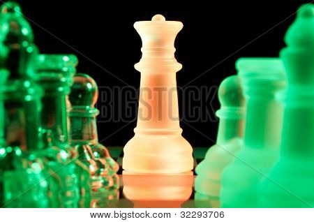 red queen and rows of green glass chess pieces is standing on board in dark