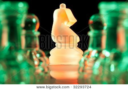 red knight and rows of green glass chess pieces is standing on board in dark