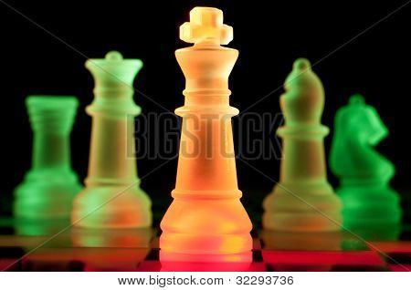 red and green glass chess pieces is standing on board in dark