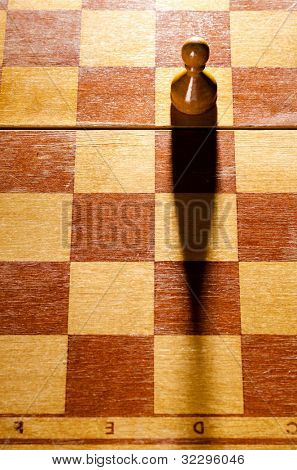 wooden chess pawn is standing on board with long shadow