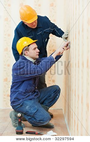 Two electrician workers at wiring cable and light switch or power wall outlet socket installation work