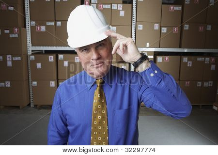 Businessman wearing hard hat and saluting in warehouse
