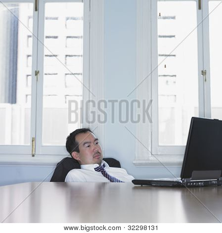 Asian businessman slouched down in his chair