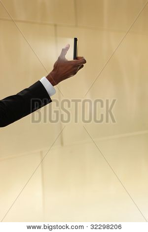 Concept photo of a man holding a glowing cell phone against neutral warm background with lots of copy space