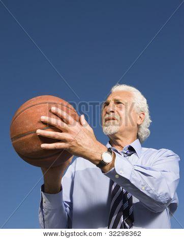 Senior Hispanic businessman getting ready to shoot a basketball