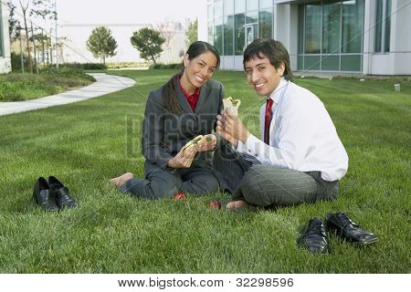 Hispanic businesswoman and businessman eating lunch in the grass