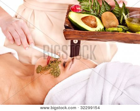 Young woman getting facial mask in spa . Isolated.