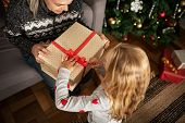 High angle view of little girl opening ribbon on christmas present box while sitting on floor. Grand poster
