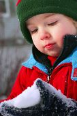 stock photo of frostbite  - a toddler looks at snow in his hand - JPG