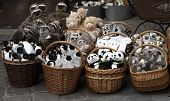 Wicker Baskets With Soft Toys On The Sidewalk. Sale Of Soft Toys: Penguins, Pandas, Sloths, Camels,  poster