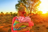 Tourist Woman Holding Ed Kissing Kangaroo Joey At Sunset Light In Australian Outback. Interacting Wi poster