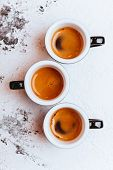 Three Cups Of Freshly Brewed Espresso Coffee On A Textured Table Top With Copyspace poster