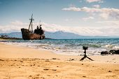 Camera On Little Tripod Taking Picture Film Video From Coastline With Rusty Shipwreck poster