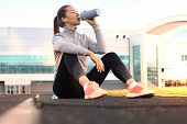 Beautiful Young Woman In Sports Clothing Drinking Water After Sport Exercise Outdoors In Stadium poster