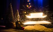 Glittering Burning Sparkler On Snow With Blurred Christmas Tree On Dark Background. New Year Holiday poster