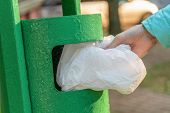 Female Hand Throws White Bag In Green Trash Can Outside On Sunny Day poster