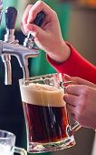 image of beer mug  - glass being filled with draft beer by barman - JPG