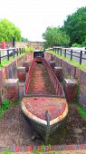 Old Narrow Boat Shell In Disused Canal Lock Chamber poster