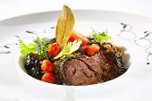 Exquisite serving white restaurent plate of grilled prime beef with tomatoes, spices and herbs close poster