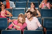 foto of misbehaving  - Young woman annoyed with boyfriend in theater - JPG