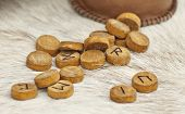 Wooden Runes With Symbols And Alphabet Close Up. Pagan Mascots Are Scattered On The Table. poster
