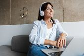 Image of a happy young woman indoors at home using laptop computer listening music with headphones s poster