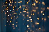 holiday, illumination and decoration concept - bokeh of christmas garland lights over dark blue back poster