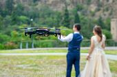 Hovering Drone Shooting Young Couple On Their Wedding In Nature. Celebration. poster
