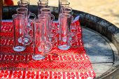 Beautiful Tall Glasses With A Handle Stand On A Textile Ethical Red Background And An Old Wooden Bar poster