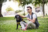 Young Blind Man With White Cane And Guide Dog Sitting In Park In City. poster