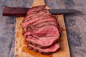 Roast Beef Slices On Wooden Cutting Board With Old Knife On Marble Background. Gourmet Food. Raw Mea poster