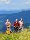 Group Of Young People In Checkered Shirts Walking Together On Top Of Mountain. Men With Guitar Hikin poster