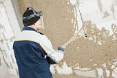 Plasterer at indoor wall renovation decoration spraying liquid plaster from plastering station