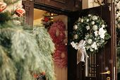 Christmas Street Decor. Stylish Christmas Wreath With Silver Ornaments On Door At Front Store At Hol poster