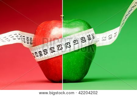 healthy food. Delicious apple with measuring tape on red background