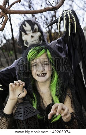 Little witch holding lantern with person costumed as grim reaper standing in background