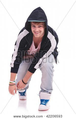 young male dancer leaning forward and sticking his tongue out with a smile. on white